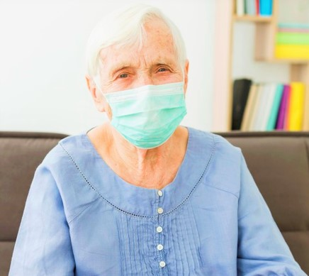 front-view-older-woman-posing-while-wearing-medical-mask_23-2148492321